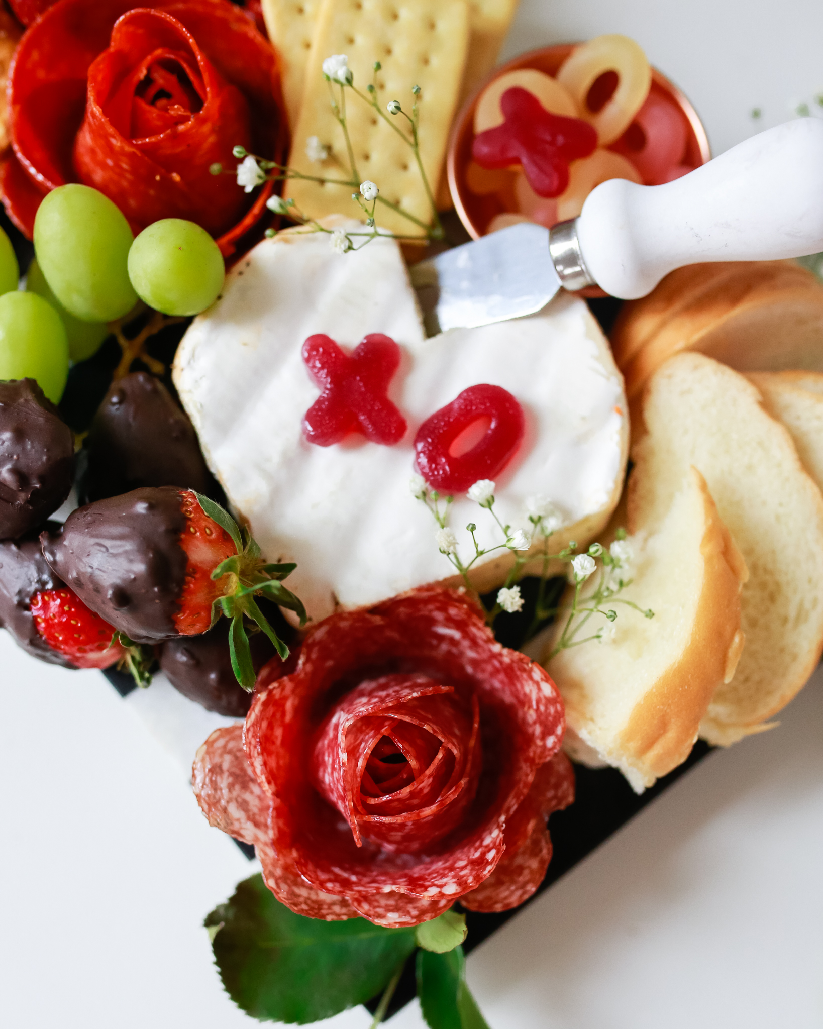 Quick and easy love themed charcuterie board with salami and pepperoni roses
